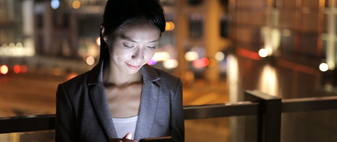 business-woman-use-of-mobile-phone-at-night-BAXAPVD
